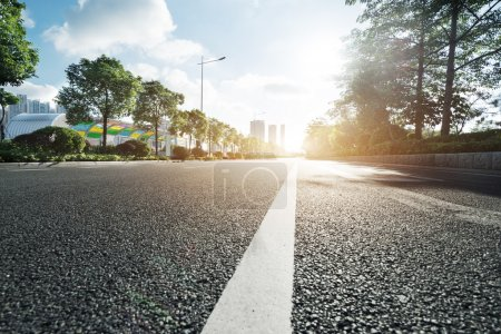 Photo for Empty asphalt road in modern city at sunrise - Royalty Free Image
