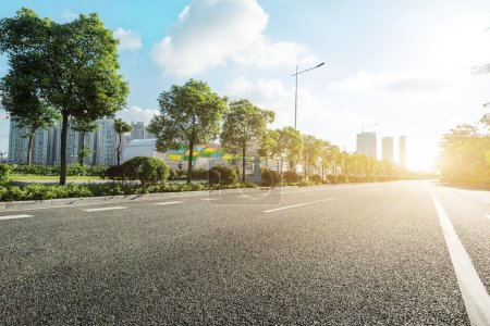 empty asphalt road in modern city at sunrise