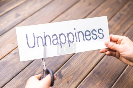 woman holds paper with word unhappiness