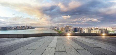 Foto de Paisaje urbano y horizonte de la nueva ciudad ribereña de Hangzhou en el cielo nuboso a la vista desde la calle vacía - Imagen libre de derechos