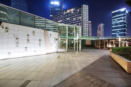 Illuminated empty footpath near modern building