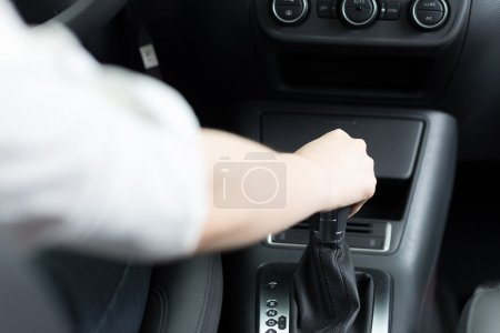 hand holding gear in car