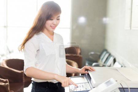 asian woman using printer in office