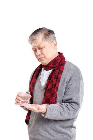 old Asian man taking pills