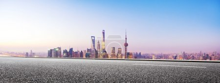 Photo for Empty asphalt road and cityscape with illuminated blue sky at dawn - Royalty Free Image