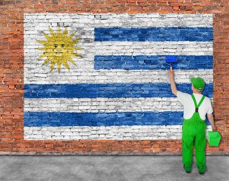 Photo pour Peintre maison peint drapeau de l'Uruguay sur vieux mur de briques - image libre de droit