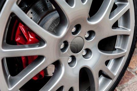 Photo pour Gros plan d'une roue sport moderne avec frein rouge - image libre de droit