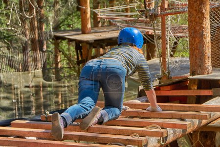 Young woman from the back in adventure rope park in Karelia