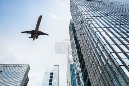 Photo pour Levant les yeux vers l'avion et le bâtiment moderne de bureaux en verre - image libre de droit
