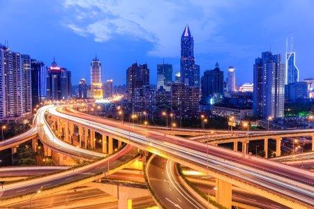 Photo pour Passage supérieur d'autoroute de shanghai avec l'horizon moderne de ville dans la tombée de la nuit - image libre de droit