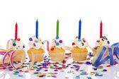 Narozeniny koláčky s svíčku a barevné konfety