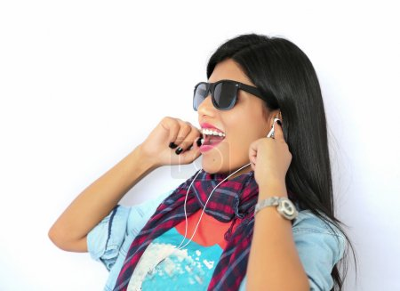 Beautiful young Indian woman listening to music with headphone a
