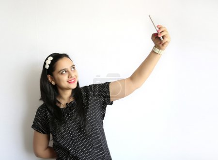 Photo for Young Indian woman take selfie of himself against the white background - Royalty Free Image