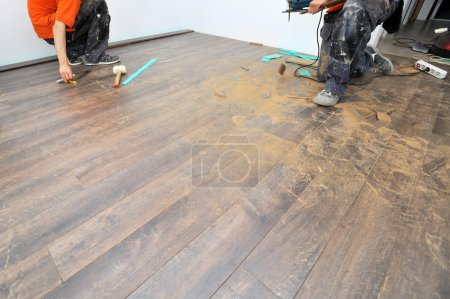 Photo for Real carpenter doing laminate floor work - Royalty Free Image
