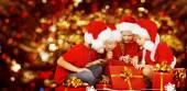 Vánoční děti otevření dárkové krabičce, šťastné děti v Santa Hat, úsměvem chlapců a dívek v červené čepici legrační hledá hračky
