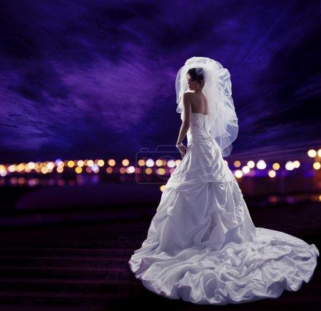 Photo pour Mariée dans la robe de mariage avec le voile, portrait de beauté de mariée de mode, long tissu drapé avec des plis, vue arrière au-dessus du ciel de lumières de ville de nuit - image libre de droit