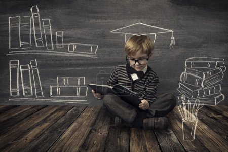 Photo for Child Little Boy in Glasses Reading Book over School Black Board with Chalk Drawing, Kids Preschool Development, Children Education Concept - Royalty Free Image