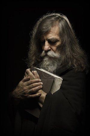 Photo pour Prière senior, vieil homme priant avec les mains sur le livre biblique, sur fond noir - image libre de droit