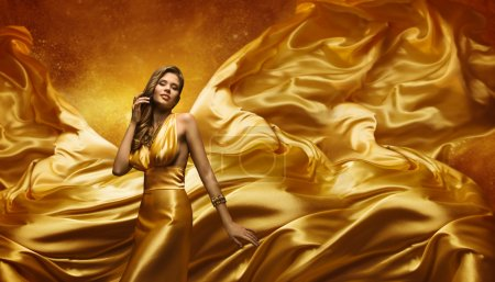 Fashion Model Gold Dress, Beauty Woman Posing, Flying Waving Cloth, Yellow Silk Fabric