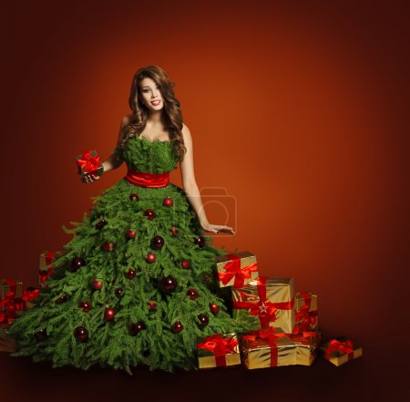 Photo pour Arbre de Noël Fashion femme robe, modèle fille et boîtes cadeaux cadeaux sur fond rouge, Concept de nouvel an - image libre de droit