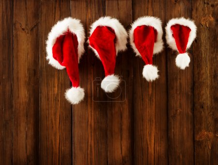 Photo for Christmas Family Santa Claus Hats Hanging on Wood Wall, Xmas Kid Hat Hang on Decorated Background - Royalty Free Image