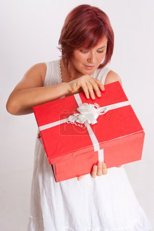 Happy red headed woman opening a present