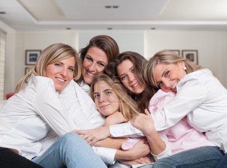 Photo pour Un groupe de cinq femmes heureuses d'âges différents embrassant dans le salon - image libre de droit