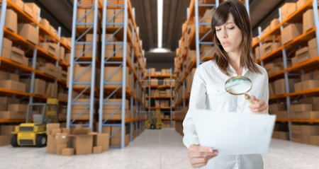 Woman inspecting document in warehouse
