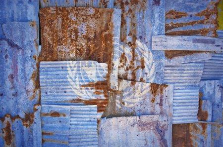 Photo pour Une image d'arrière-plan abstraite du drapeau de l'ONU peintes sur ondulée rouillée qui se chevauchent pour former un mur ou une clôture - image libre de droit