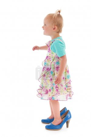 Toddler girl standing inmothers big shoes isolated...