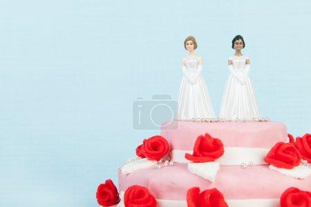 Foto de Rosa pastel de bodas con rosas rojas y pareja de lesbianas en la parte superior sobre fondo azul - Imagen libre de derechos