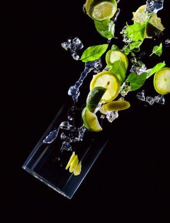Photo pour Lime, citron et feuilles de menthe poivrée sur fond noir - image libre de droit