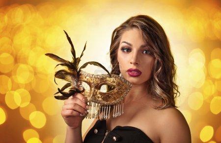 Photo pour Belle femme en robe noire avec masque de carnaval d'or - image libre de droit
