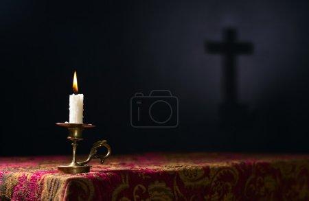 Photo pour Bougie sur fond sombre avec la silhouette de la croix, mise au premier plan - image libre de droit