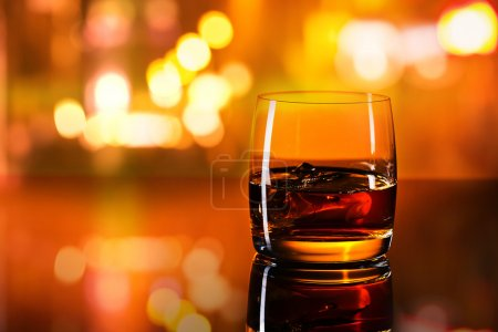 Photo for Whiskey with ice on a glass table in bab - Royalty Free Image
