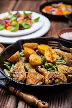 Chicken legs in pan with potatoes and salad