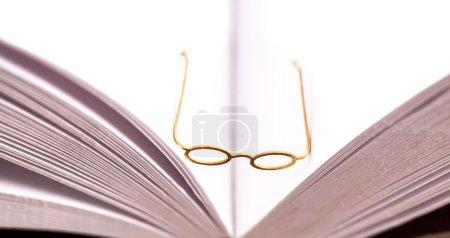 Photo pour Petits verres de lecture assis à l'intérieur de la colonne vertébrale d'un livre blanc ouvert avec des pages blanches - image libre de droit