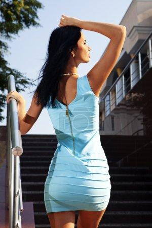 Photo pour Belle brune en robe bleue va sur les marches - image libre de droit