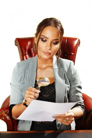 Business woman looks on one document by magnifying...
