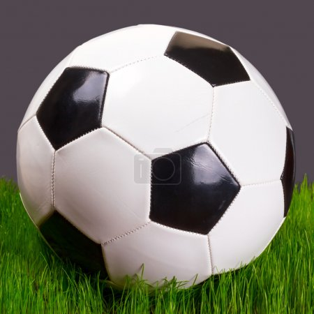 Soccer ball on the grass over black background...