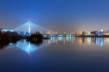 Vistula river scenery with cable-stayed illuminated bridge in Warsaw