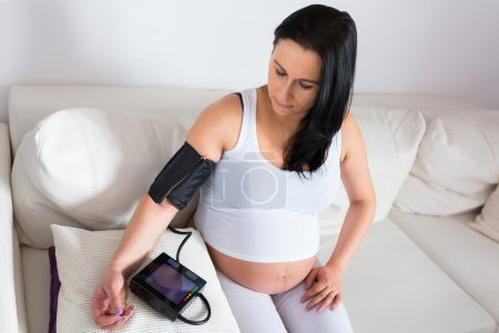 Photo for Pregnant woman measures the blood pressure - Royalty Free Image