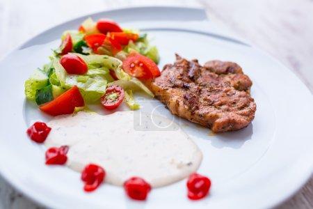 Photo pour Steak de porc grillé avec salade dans l'assiette - image libre de droit
