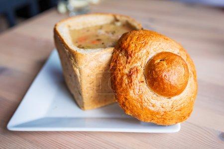 Photo pour Soupe savoureuse servie dans un bol à pain cuit sur la table - image libre de droit