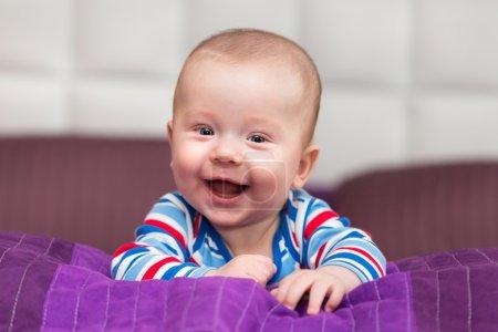 Photo pour Bébé garçon souriant allongé sur son ventre - image libre de droit