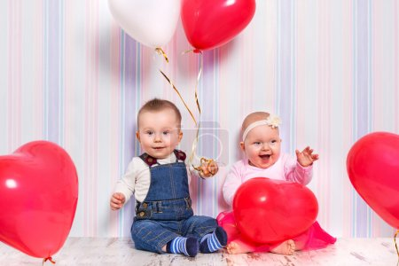 Baby boy and girl with heart balloons for valentines