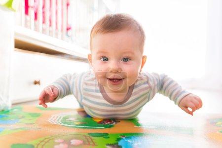 Foto de Bebé niño gatear en el suelo ay casero - Imagen libre de derechos