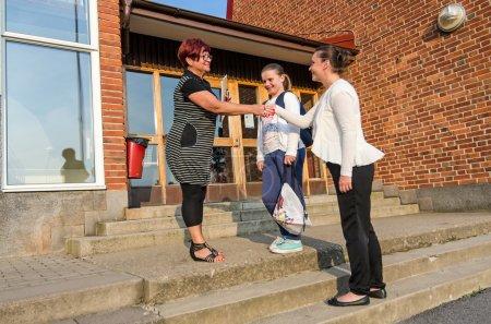 Welcome handshake between schoolgirl mother and teacher