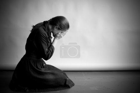 Photo for Woman is sitting in profile on an old cracky floor. She is sad and depressed, crying and covering her face with hands. Studio paper  background in behing her. - Royalty Free Image