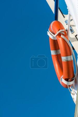Orange lifebuoy on a white yacht